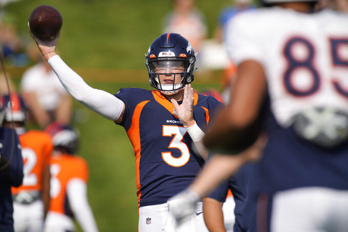 Denver Broncos quarterback Drew Lock, back, passes the ball to tight end Albert Okwuegbunam as they take part in drills during an NFL football training camp at the team's headquarters Tuesday, Aug. 17, 2021, in Englewood, Colo. (AP Photo/David Zalubowski)