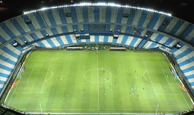 Players of Peru's Alianza Lima and Argentina's Racing Club play a Copa Libertadores soccer match at the Presidente Peron stadium in Buenos Aires, Argentina, Thursday, March 12, 2020. The match was played in an empty, closed door stadium as part of the government's measures to contain transmission of the new coronavirus. For most people the new coronavirus causes only mild or moderate symptoms, such as fever and cough. For some, especially older adults and people with existing health problems, it can cause more severe illness including pneumonia. (AP Photo/Gustavo Garello)