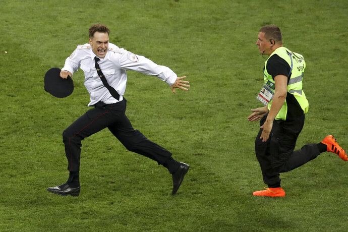 FILE - In this Sunday, July 15, 2018 file photo, Pyotr Verzilov invading the pitch, runs away as a steward tries to stop him during the France and Croatia 2018 World Cup final match in the Luzhniki Stadium in Moscow, Russia. Russian state news agency Tass says a prominent member of the protest group Pussy Riot has been detained by the police anti-extremism division. The Mediazona website reported that Pyotr Verzilov was seized at his apartment by unidentified men who broke down the door on Sunday, June 21, 2020.  (AP Photo/Thanassis Stavrakis, File)