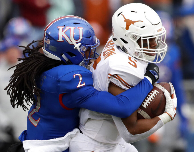 Texas running back Tre Watson (5) is tackled by Kansas cornerback Corione Harris (2) during the first half of an NCAA college football game in Lawrence, Kan., Friday, Nov. 23, 2018. (AP Photo/Orlin Wagner)