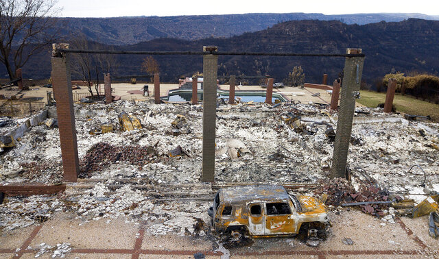 FILE - In this Dec. 3, 2018, file photo, a vehicle rests in front of a home leveled by the Camp Fire in Paradise, Calif. California power regulators are weighing a recommendation to back off plans to fine Pacific Gas and Electric an additional $462 million for igniting a series of Northern California 2018 deadly wildfires rather than risk that the harsher punishment will scuttle the utility's plan to emerge from bankruptcy protection, the state's Public Utilities Commission said in a document made public Monday, March 30, 2020. (AP Photo/Noah Berger, File)