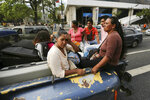 Commuters ride in the bed of a private truck during a power outage that suspended the subway service in Caracas, Venezuela, Monday, March 25, 2019. (AP Photo/Fernando Llano)