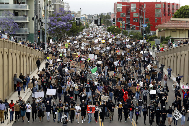 Protestors march Thursday, June 4, 2020, in San Diego. Protests continue to be held in U.S. cities, sparked by the death of George Floyd, a black man who died after being restrained by Minneapolis police officers on May 25. (AP Photo/Gregory Bull)