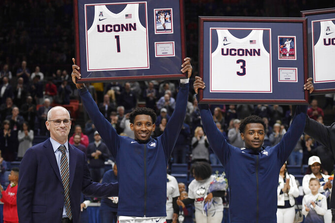 Connecticut's Christian Vital (1) and Alterique Gilbert (3) stand by head coach Dan Hurley as they are honored on Senior Night before an NCAA college basketball game against Houston, Thursday, March 5, 2020, in Storrs, Conn. (AP Photo/Jessica Hill)