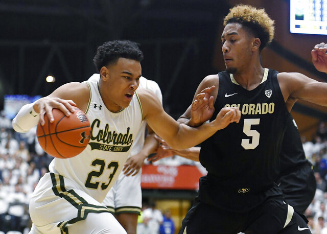 Colorado State guard John Tonje, left, drives past Colorado guard D'Shawn Schwartz in the first half of an NCAA college basketball game in Fort Collins, Colo., Friday, Dec. 13, 2019. (Bethany Baker/Fort Collins Coloradoan via AP)