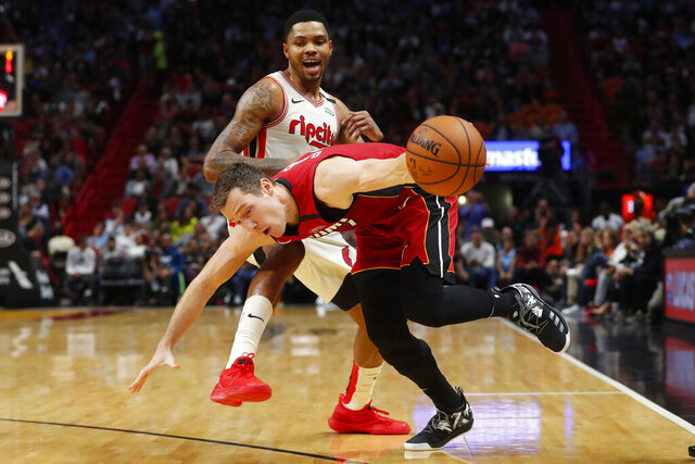 Miami Heat guard Goran Dragic, foreground, looses control of the ball as he drives past Portland Trail Blazers guard Kent Bazemore during the second half of an NBA basketball game, Sunday, Jan. 5, 2020, in Miami. Dragic had 29 points and 13 assists as the Heat defeated the Trail Blazers 122-111. (AP Photo/Wilfredo Lee)