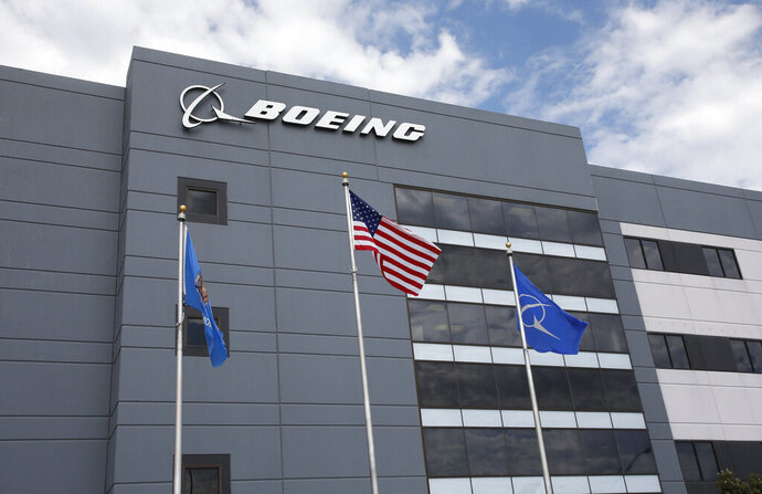 FILE - In this May 14, 2019, file photo flags fly outside the main building of The Boeing Company's Oklahoma City facility in Oklahoma City. Boeing Co. reports financial earns on Wednesday, Oct. 23. (AP Photo/Sue Ogrocki, File)