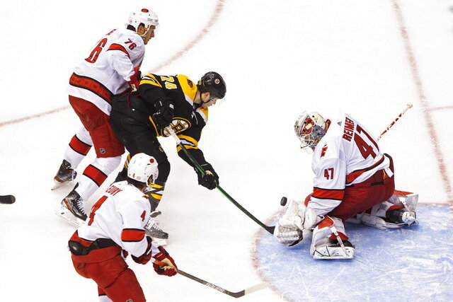 Carolina Hurricanes goaltender James Reimer (47) makes a save against Boston Bruins' Jake DeBrusk (74) as Hurricanes' Brady Skjei (76) defends during second-period NHL hockey first-round Stanley Cup playoff action in Toronto, Thursday, Aug. 13, 2020. (Chris Young/The Canadian Press via AP)