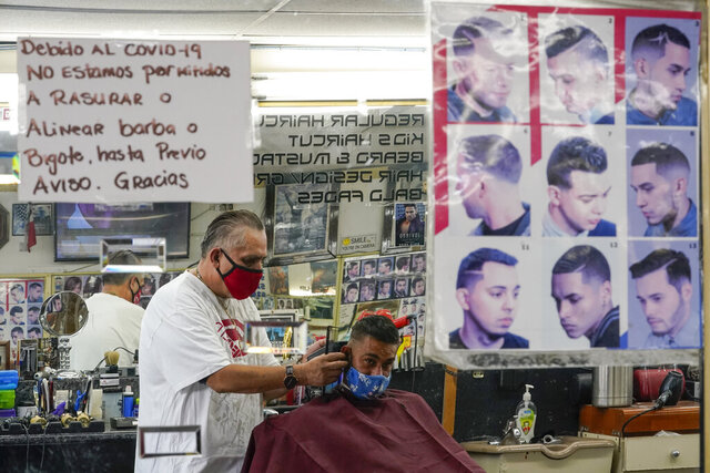 Edgar Gomez has his hair cut by George Garcia, owner of George's Barber Shop, Tuesday, July 14, 2020, in San Pedro, Calif. Gov. Gavin Newsom this week ordered that indoor businesses like salons, barber shops, restaurants, movie theaters, museums and others close due to the spread of COVID-19. (AP Photo/Ashley Landis)