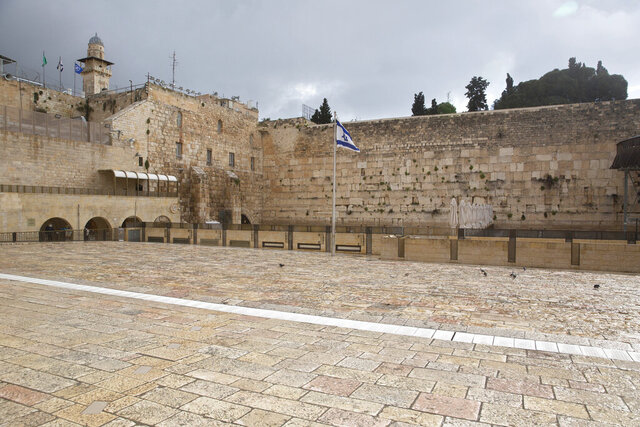 The Western Wall, the holiest site where Jews can pray, in Jerusalem's Old City, is empty Friday, April 10, 2020. Christians are commemorating Jesus' crucifixion without the solemn church services or emotional processions of past years, marking Good Friday in a world locked down by the coronavirus pandemic. (AP Photo/Sebastian Scheiner)