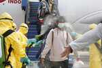 FILE - In this Sunday, Feb. 2, 2020, file photo released by the Indonesian Foreign Ministry, Indonesians who arrived from Wuhan, China, are sprayed with antiseptic at Hang Nadim Airport in Batam, Indonesia. Health authorities are scrambling to halt the spread of a new virus that has killed hundreds in China. But with important details about the illness and how it spreads still unknown, officials and medical personnel are struggling. (Indonesian Foreign Ministry via AP)