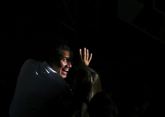 National Assembly President Juan Guaido greets supporters as he arrives to meet with residents in the Hatillo municipality of Caracas, Venezuela, Thursday, March 14, 2019. Guaido has declared himself interim president and demands new elections, arguing that President Nicolas Maduro's re-election last year was invalid. (AP Photo/Fernando Llano)