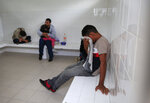 A young man cries as he says that if he gets sent back to Honduras, he will be killed, while sitting with other migrants inside an immigration holding cell after being removed from a bus heading north out of Comitan, Chiapas state, Mexico, Sunday, June 16, 2019. Behind is Honduran migrant Noe, 31, holding his 4-year-old daughter Marlene. Mexican President Andrés Manuel López Obrador said Saturday his country must help Central Americans fleeing poverty and violence, even as it increases security and revisions to deter migrants from passing through Mexico on route to the U.S. (AP Photo/Rebecca Blackwell)