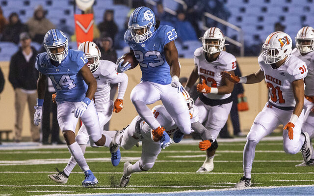 North Carolina's Josh Henderson (23) leaps to try to avoid a tackle from Mercer's Kendall Bohler (29) during the second half of an NCAA college football game in Chapel Hill, N.C., Saturday, Nov. 23, 2019. (AP Photo/Ben McKeown)