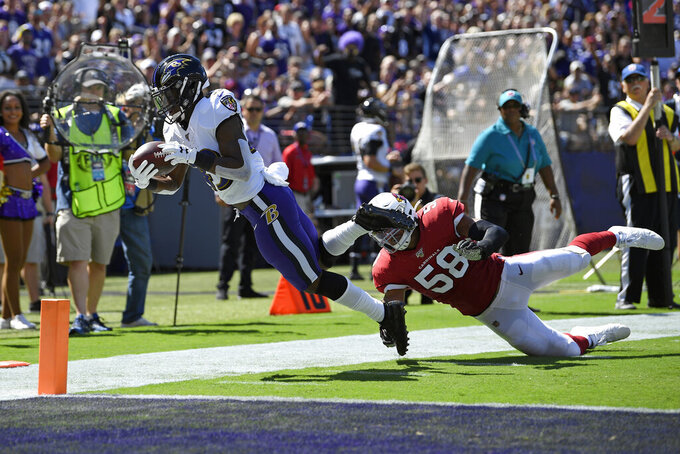 Baltimore Ravens running back Justice Hill, left, dives but is unable to score a touchdown as he is tackled by Arizona Cardinals middle linebacker Jordan Hicks in the first half of an NFL football game, Sunday, Sept. 15, 2019, in Baltimore. (AP Photo/Nick Wass)