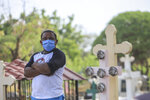 A person wears a mask as he attends a funeral at the Central cemetery of Managua, Nicaragua, Monday, May 11, 2020. President Daniel Ortega's government has stood out for its refusal to impose measures to halt the new coronavirus for more than two months since the disease was first diagnosed in Nicaragua. Now, doctors and family members of apparent victims say, the government has gone from denying the disease's presence in the country to actively trying to conceal its spread. (AP Photo/Alfredo Zuniga)