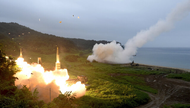 FILE - In this July 29, 2017, file photo provided by South Korea Defense Ministry, South Korea's Hyunmoo II Missile system, left, and a U.S. Army Tactical Missile System, right, fire missiles during a combined military exercise between the two countries against North Korea at an undisclosed location in South Korea. South Korea said Tuesday, July 28, 2020, it has won U.S. consent to use solid fuel for space launch vehicles, a move that experts say would enable Seoul to launch its first surveillance satellites and accumulate technology to build more powerful missiles. (South Korea Defense Ministry via AP, File)