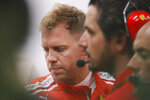 Ferrari driver Sebastian Vettel of Germany, left, talks with team mechanics during second practice at the Marina Bay City Circuit ahead of the Singapore Formula One Grand Prix in Singapore, Friday, Sept. 14, 2018. (AP Photo/Vincent Thian)