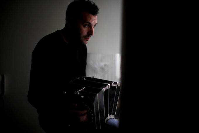 Tango dancer and musician Nicolas Ponce poses for a portrait as he plays the bandoneon inside a plant shop he started after the COVID-19 pandemic lockdown closed dance venues in Buenos Aires, Argentina, Friday, June 4, 2021. The essence of tango, he said, is what makes it so difficult to perform in the current health emergency. (AP Photo/Natacha Pisarenko)