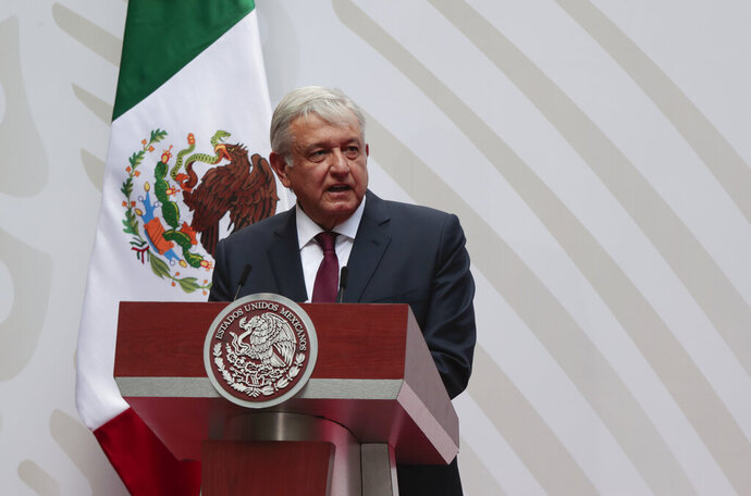 FILE - In this April 5, 2020 file photo, Mexican President Andres Manuel Lopez Obrador speaks at the National Palace in Mexico City. Over the May 17, 2020 weekend, the administration of President Lopez Obrador has cited the coronavirus pandemic as a justification for new rules that will reduce the role of renewable energies like solar and wind power, granting a reprieve to the government's own ageing, fossil-fuel power plants.  (AP Photo/Eduardo Verdugo, File)