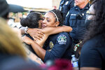 FILE - In this June 4, 2020, file photo police officer Alexandra Parker hugs a protester at the Austin Police Department headquarters during a Black Lives Matter rally in Austin. (Lola Gomez/Austin American-Statesman via AP, File)/