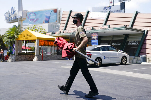 Chasen Weiss, whose family owns Mel's Drive-In, wears a mask while working, Thursday, July 2, 2020, in West Hollywood, Calif. Sheriff's deputies in West Hollywood will issue citations to people who are not wearing masks in public, ramping up enforcement that previously had largely been imposed without penalties. (AP Photo/Ashley Landis)