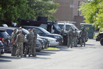 Tactical police stage in a Safeway parking lot on Belair Road near Chapel Road in response to the death of a Baltimore County police officer in Perry Hall, Md., May 21, 2018. Rifle-toting police swarmed into the Baltimore suburb where a female officer was fatally injured Monday, searching for suspects believed to be armed after witnesses reported hearing a pop and seeing the officer run over by a Jeep. (Jerry Jackson/The Baltimore Sun via AP)