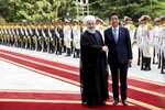 Japanese Prime Minister Shinzo Abe, right, shakes hands for the cameras with Iranian President Hassan Rouhani, during the official arrival ceremony, at the Saadabad Palace in Tehran, Iran, Wednesday, June 12, 2019. The Japanese leader is in Tehran on a mission to calm tensions between the U.S. and Iran. (AP Photo/Ebrahim Noroozi)