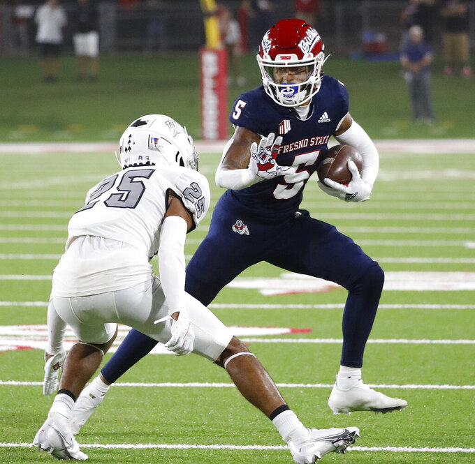 Fresno State wide receiver Jalen Cropper looks to avoid UNLV defensive back Cameron Oliver during the first half of an NCAA college football game in Fresno, Calif., Friday, Sept. 24, 2021. (AP Photo/Gary Kazanjian)