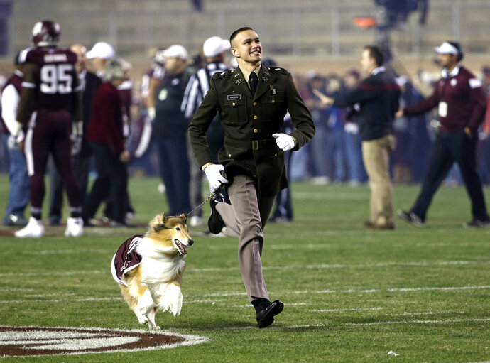 File-This Nov. 27. 2014, file photo shows Texas A&M cadet Ryan Kreider running onto the field with mascot Reveille VIII before an NCAA college football game against LSU in College Station, Texas.  A service has been scheduled Aug. 30 at Kyle Field to remember late Texas A&M collie mascot Reveille VIII. Organizers say Reveille VIII will be laid to rest 10 years to the day from her debut as mascot. The revered 12-year-old dog had been ill and died June 25. Reveille VIII drew avoidance attention on Sept. 20, 2014, as then-A&M cadet handler Kreider  deflected SMU receiver Der'rikk Thompson away from the dog. Kreider gained fame for throwing himself in front of the out-of-bounds player. Kreider has been invited to attend the service this month outside the north end of Kyle Field. (AP Photo/David J. Phillip, File)