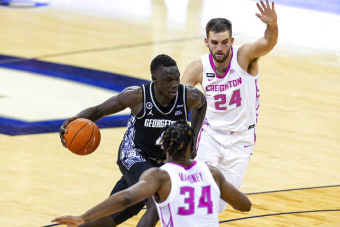 Georgetown forward Chudier Bile (4) drives the basket against Creighton guard Mitch Ballock (24) and guard Denzel Mahoney (34) during the second half of an NCAA college basketball game Wednesday, Feb. 3, 2021, in Omaha, Neb. (AP Photo/John Peterson)