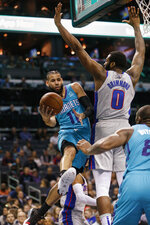 Charlotte Hornets forward Cody Martin, left, passes the ball around Detroit Pistons center Andre Drummond during the first half of an NBA basketball game in Charlotte, N.C., Friday, Nov. 15, 2019. (AP Photo/Nell Redmond)