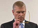 """FILE - In this file photo dated Thursday, Jan. 22, 2015, Britain's Prince Andrew, puts on his glasses prior to his speech to business leaders during a reception at the sideline of the World Economic Forum in Davos. Britain's Prince Andrew said Wednesday Nov. 20, 2019, that he is stepping back from public duties with the queen's permission, saying that recent disclosures regarding his association with the late convicted sex offender Jeffrey Epstein have become a """"major distraction"""" to the royal family's work. (AP Photo/Michel Euler, FILE)"""
