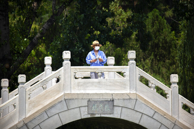 A man wearing a face mask to protect against the new coronavirus stands on a footbridge at a public park in Beijing, Wednesday, June 10, 2020. China says its three latest cases of coronavirus infection were brought from outside the country. No new deaths were reported Wednesday and just a few dozen people remain in treatment for COVID-19. (AP Photo/Mark Schiefelbein)