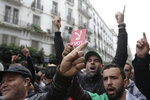 Algerian demonstrators take to the streets in the capital Algiers to reject the presidential elections, in Algiers, Algeria, Friday, Dec. 13, 2019. Abdelmadjid Tebboune, a former Algerian prime minister and loyalist of Algeria's influential army chief, has been elected Algeria's new president. Tebboune, 74, was elected with 58.15% of the vote in this oil-rich North African country. Banner in Arabic reads