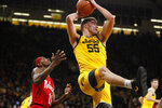 Iowa center Luka Garza (55) grabs a rebound over Nebraska guard Dachon Burke Jr., left, during the first half of an NCAA college basketball game, Saturday, Feb. 8, 2020, in Iowa City, Iowa. (AP Photo/Charlie Neibergall)