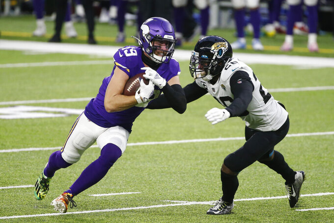 Minnesota Vikings wide receiver Adam Thielen runs from Jacksonville Jaguars safety Jarrod Wilson, right, during overtime in an NFL football game, Sunday, Dec. 6, 2020, in Minneapolis. The Vikings won 27-24. (AP Photo/Bruce Kluckhohn)