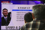 People watch a TV showing an image of Jo Song Gil, the North Korea's former ambassador to Italy, during a news program at the Seoul Railway Station in Seoul, South Korea, Wednesday, Oct. 7, 2020. Jo who had vanished in Italy in late 2018, lives in South Korea under government protection, a lawmaker said Wednesday. The Korean letters read: