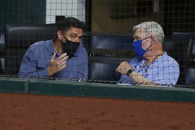 FILE - In this Aug. 12, 2020, file photo, Texas Rangers general manager Jon Daniels, left, talks with Ray Davis, one of the team's owners, during the fourth inning of the Rangers' baseball game against the Seattle Mariners in Arlington, Texas. Davis and the Rangers ownership had hoped for the chance to win the World Series in their first season in their new ballpark. The World Series will be played in the new $1.2 billion stadium, but without the Rangers. Globe Life Field will be a neutral site for two National League playoffs series before the World Series. (AP Photo/Tony Gutierrez, File)