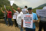Lebanese protesters hold placards during a protest against the Bisri dam project, in the Bisri Valley, 58 kilometers (36 miles) southeast of Beirut, Lebanon, Saturday, June. 15, 2019. Its expansive lands of pine, citrus trees and ancient ruins are about to turn into a controversial mega dam funded by the World Bank. For years now, activists and locals have voiced their opposition to what they describe as not only