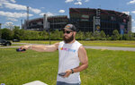 Cody Underwood of Knoxville, Tennessee uses a remote to fix the signal on a large TV set up so he and his friends could watch the live NASCAR race Sunday afternoon at Bristol Motor Speedway. (Andre Teague/Bristol Herald Courier via AP)