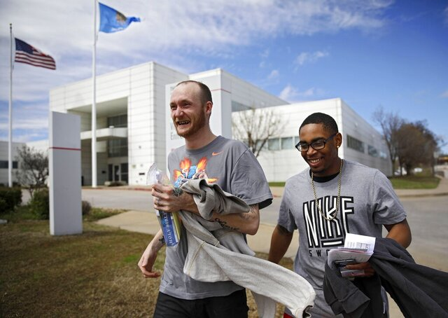 Gary Poindexter, left, and Christopher Brown laugh as they leave the at the David L. Moss Criminal Justice Center after being released Thursday, March 19, 2020 in Tulsa, Oka.. A special docket was created to expedite release of those locked up on low level offenses due to the COVID-19 outbreak. (Mike Simons/Tulsa World via AP)