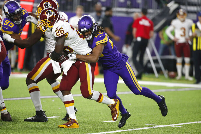 Washington Redskins running back Adrian Peterson (26) is tackled by Minnesota Vikings cornerback Trae Waynes, right, during the second half of an NFL football game, Thursday, Oct. 24, 2019, in Minneapolis. (AP Photo/Bruce Kluckhohn)