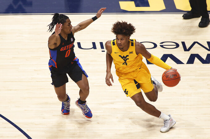 West Virginia guard Miles McBride (4) is defended by Florida guard Ques Glover (0) during the first half of an NCAA college basketball game Saturday, Jan. 30, 2021, in Morgantown, W.Va. (AP Photo/Kathleen Batten)