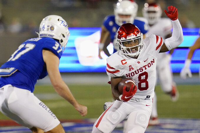 Houston running back Chandler Smith (8) carries past Tulsa safety Hunter Rangel (37) in the first half of an NCAA college football game Friday, Oct. 1, 2021, in Tulsa, Okla. (AP Photo/Sue Ogrocki)