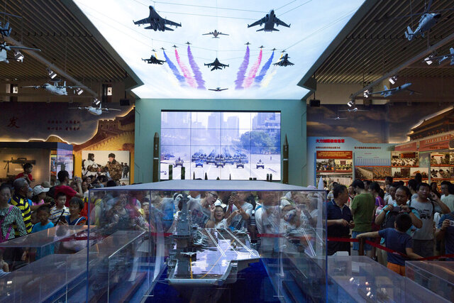 FILE - In this Aug. 1, 2017, file photo, visitors look at a scale model of a Chinese aircraft carrier during an exhibition to mark the 90th anniversary of the founding of the People's Liberation Army at the military museum in Beijing. China is protesting the alleged incursion of a U.S. Air Force U-2 spy plane into a no-fly zone imposed during live-fire military exercises in the country's north in a statement issued Tuesday, Aug. 25, 2020. (AP Photo/Ng Han Guan, File)