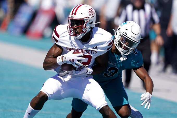 Massachusetts wide receiver Melvin Hill is tackled by Coastal Carolina cornerback Jacob Proche during the first half of an NCAA college football game on Saturday, Sept. 25, 2021, in Conway, S.C. (AP Photo/Chris Carlson)