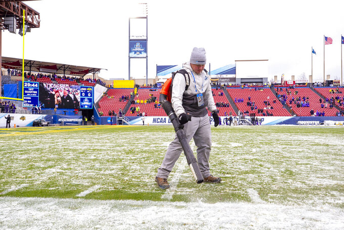 A worker blows snow off the field before the FCS championship NCAA college football game between North Dakota State and James Madison, Saturday, Jan. 11, 2020, in Frisco, Texas. (AP Photo/Sam Hodde)