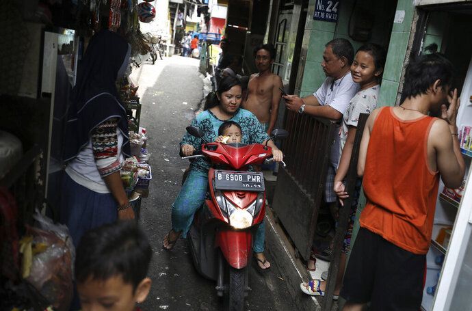 A motorist rides past as residents talk on an alley at a low-income neighborhood in Jakarta, Indonesia, March 23, 2020. As the virus spreads, the World Health Organization has pointed out that the future of the pandemic will be determined by what happens in some of the world's poorest and most densely populated countries. From Mumbai to Rio de Janeiro to Johannesburg the question is: What do you do if there is no space to socially distance yourself from others in some of world's most unequal regions? (AP Photo/Dita Alangkara)