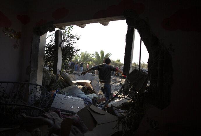 Un niño palestino cruza un agujero en la pared de una casa destrozada tras un ataque aéreo israelí nocturno, en Khan Younis, en el sur de la Franja de Gaza, el 14 de noviembre de 2019. (AP Foto/Khalil Hamra)